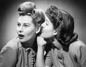 Two women gossiping in studio (B&W)